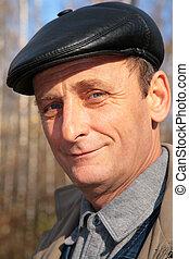 Portrait of elderly man in black hat in wood in autumn