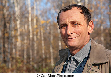 Portrait of elderly man in wood in autumn