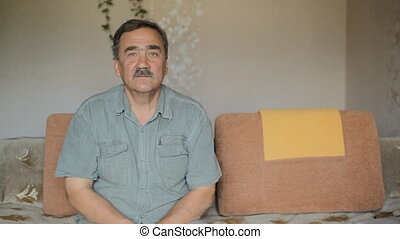Portrait of elderly man with a mustache looking at camera at home on sofa