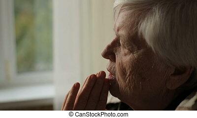Portrait of elderly praying woman