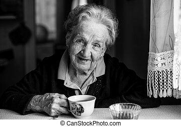 Portrait of elderly woman drinking tea, black-and-white photo.