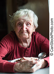 Portrait of elderly woman eats sitting at the table.