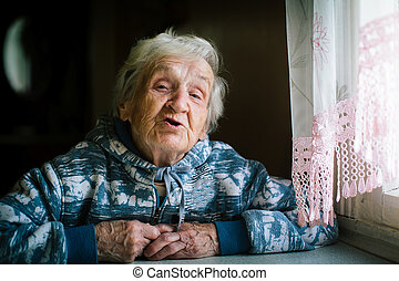 Portrait of elderly woman in the house at the table.