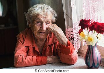 Portrait of elderly woman near window in the house.