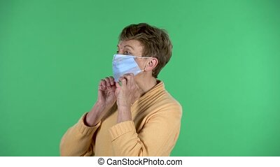 Portrait of elderly woman puts a medical mask on her face to protecting yourself from coronavirus pandemic isolated over green background. Profile view