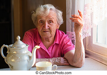 Portrait of elderly woman sitting at the kitchen table.