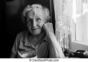 Portrait of elderly woman sitting at the table.