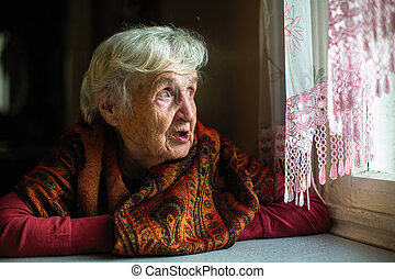 Portrait of elderly woman sitting in the house looks out the window.