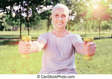 Portrait of elderly woman training with weights
