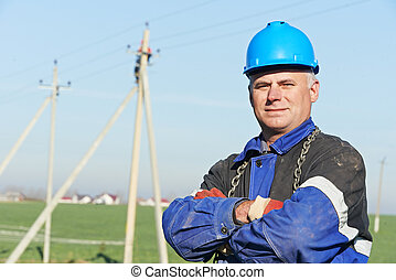 Portrait of power line repairman electrician worker on electric post pole work