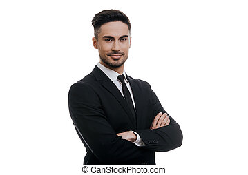 Portrait of elegance.  Handsome young smiling man in full suit looking at camera and keeping arms crossed while standing against white background