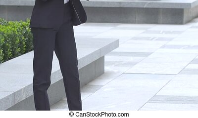 elegant blonde business woman with tablet computer near office building