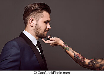 Portrait of elegant brutal man in a suit with a female ...