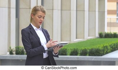 elegant business woman with tablet computer near office building