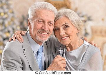 elderly couple ear christmas tree