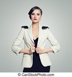 Portrait of elegant fashion model woman in black dress on white wall background