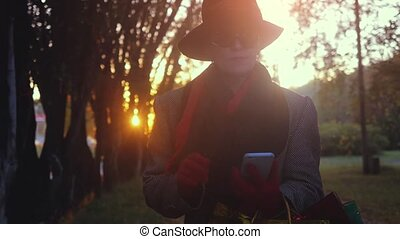 Portrait of elegant mature woman using smart phone goes from shopping mall with bags in autumn park during sunset in slowmotion. 1920x1080