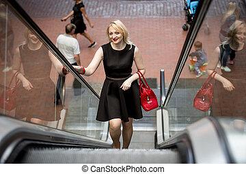 elegant stylish woman using escalator at shopping mall