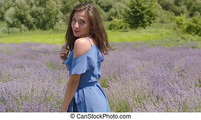 Beautiful joyful young female in stylish blue dress posing in blooming lavender field. Stunning long brown hair woman looking tempting and playful, expressing appeal and allure in summer nature.