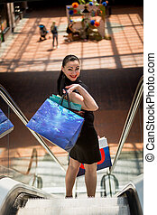 elegant woman with shopping bags standing on escalator at mall