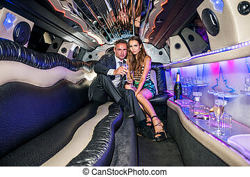 Portrait of elegant young couple with champagne flutes in limousine