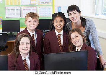 Portrait Of Elementary School Pupils With Teacher In Computer Class