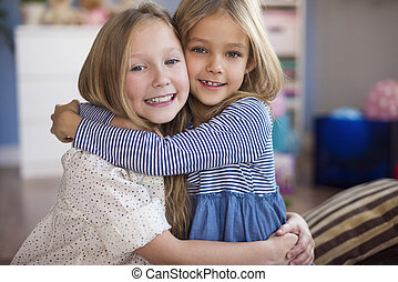 Portrait of embracing sisters in the living room