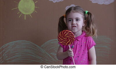 portrait of emotional girl with big sugar lollipop, kid eat sweets. Beautiful little girl with lollipop