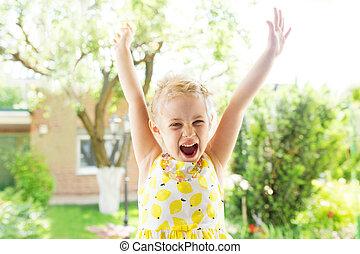 Portrait of emotional little girl in summer dress outdoor
