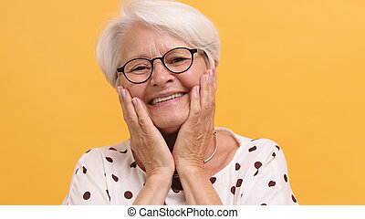 Portrait of emotional smiling senior happy woman holding hands on her cheeks