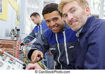 portrait of engineer and apprentice by machinery controls