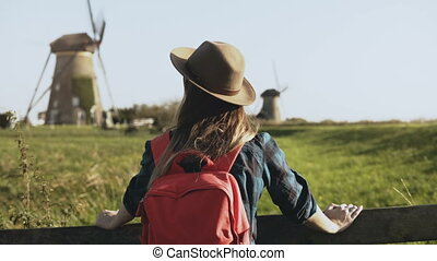 Portrait of European girl near rustic windmill. Attractive...