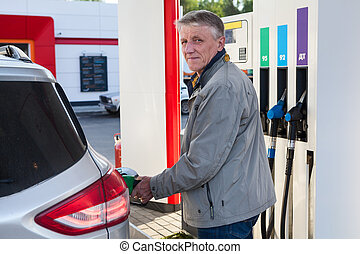 Portrait of European mature man refueling own car on gas station at summer day