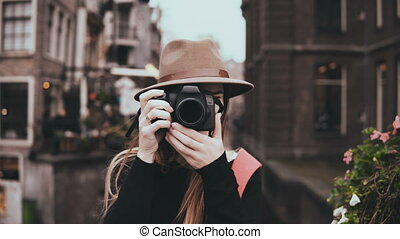 Portrait of excited female blogger with a camera. Pretty...