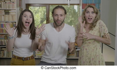 Portrait of excited group of friends yelling with wide open...