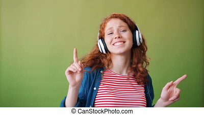 Portrait of excited teenager in headphones dancing chilling listening to music