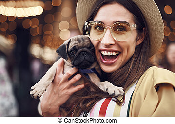 Portrait of excited woman holding cute little puppy - Loving...