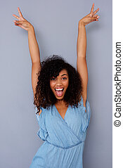 excited young african american woman smiling with hands raised against gray background