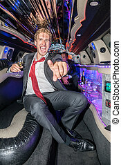 Portrait of excited young man holding champagne flute while gesturing in limo