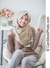 excited young woman with hijab smiling while sitting on a couch