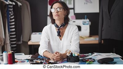 Portrait of exhausted female designer sitting at in casual outfit lost her inspiration while working with clothing collection at studio. Concept of creativity and fashion industry.