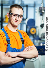 Portrait of young adult experienced industrial worker over industry machinery production line manufacturing workshop