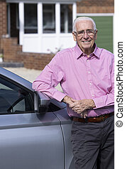 Portrait Of Experienced Senior Male Driver Standing Next To Car