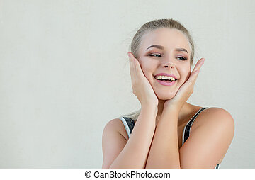 Portrait of expressive blonde girl with natural makeup posing at white background. Empty space