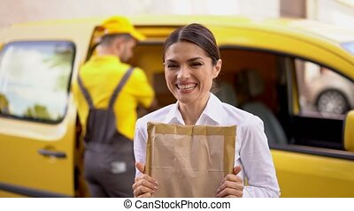 Portrait of extremely happy woman receiving her package. -...