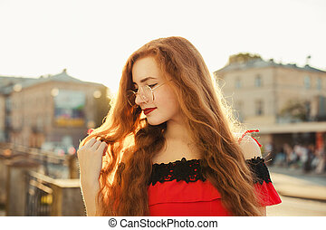 Portrait of fabulous redhead woman with freckles wearing glasses, posing in evening soft sunlight. Empty space
