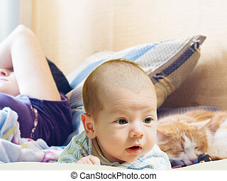 Portrait of face funny caucasian newborn toddler baby boy with sleeping mother and cat
