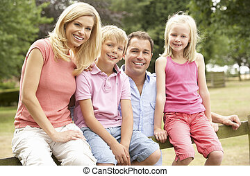 Portrait Of Family Sitting On Fence In Countryside