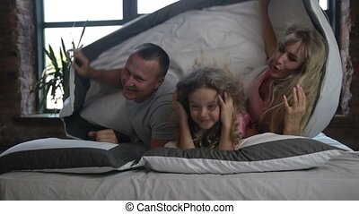 Portrait of family with daughter posing in bed