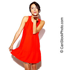 Portrait of fashion cute young girl model in a red dress on a white background giving a kiss